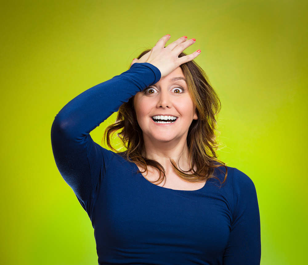 Closeup portrait excited young middle aged woman placing hand on head, palm on face gesture in duh moment, isolated green background. Human emotion facial expression feelings, body language, reaction